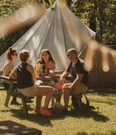 Photo of a family bonding outside a tent