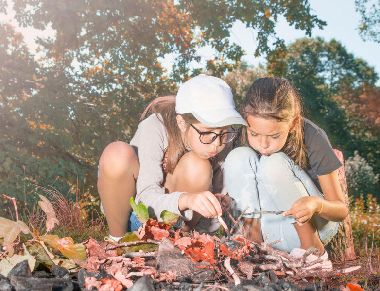 Photo of girls in the forest making fire in the woods