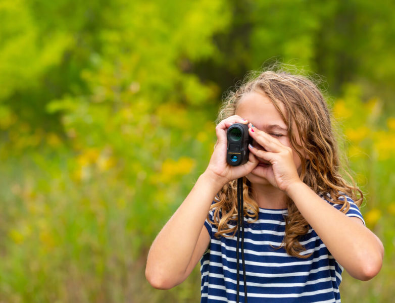 This is an image of a young girl using a rangefinder on a flower field.
