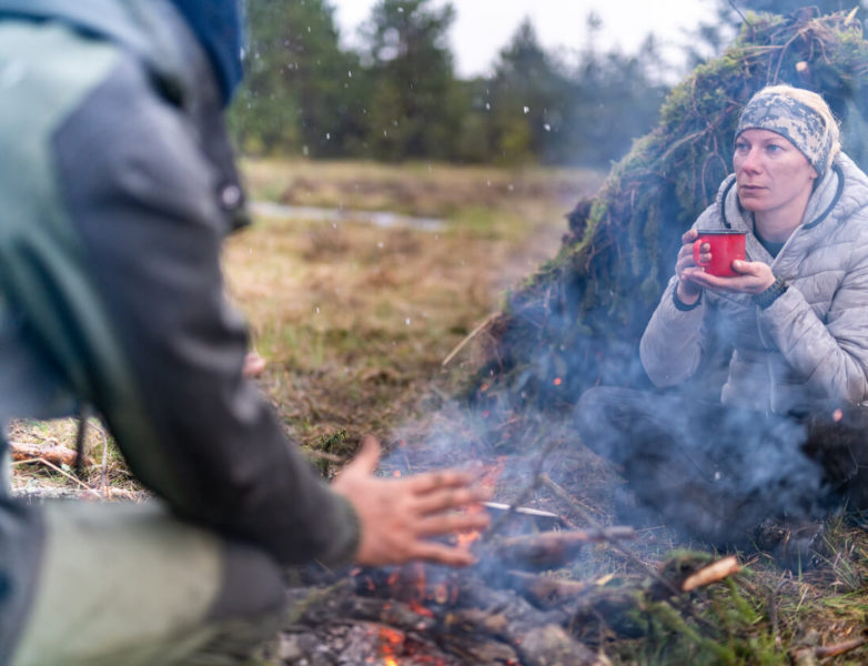 Photo of a Woman drinking tea and a man warms his hands next to a campfire
