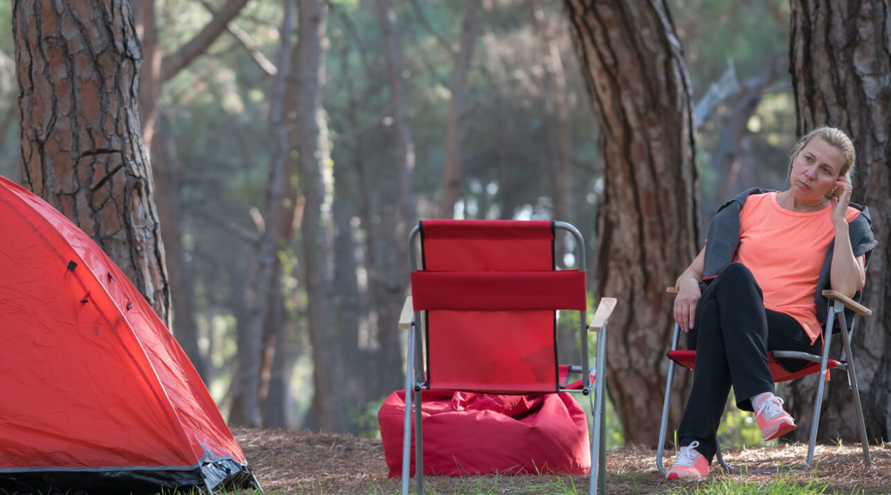 Image of a thinking woman sitting in a red Chair at a camping site outdoors
