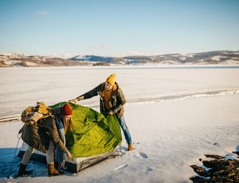 Photo of couple preparing their tent for resting