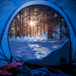 Photo of a snowy forest in winter, view from tent