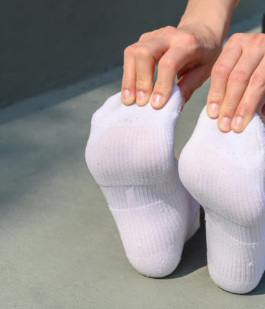A person stretching his feet wearing a white socks before running.