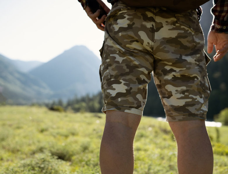 A person facing the meadow, standig with one hand on his waist, wearing a militar-printed cargo short.