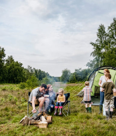 Image of a family camping with a huge four room tent behind them.