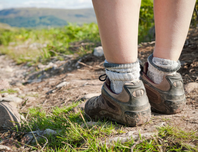 Photo of a woman's legs and muddy feet in close-up on a hiking path