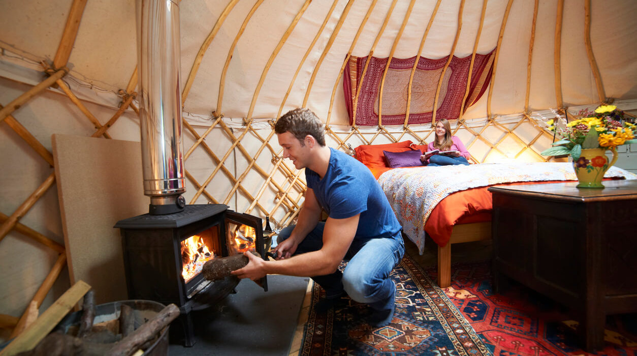 Image of a man sitting in front of a camping tent stove inside a tent.