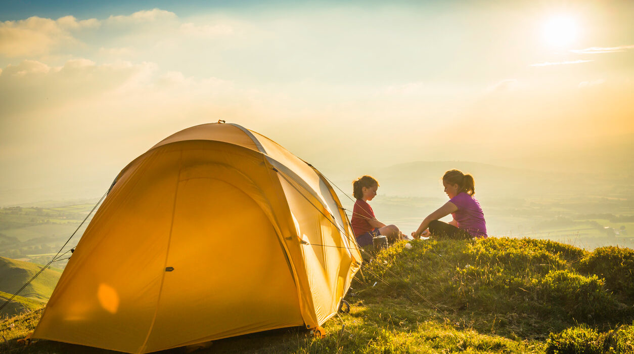 A photo of a yellow tent and two girls at the clift