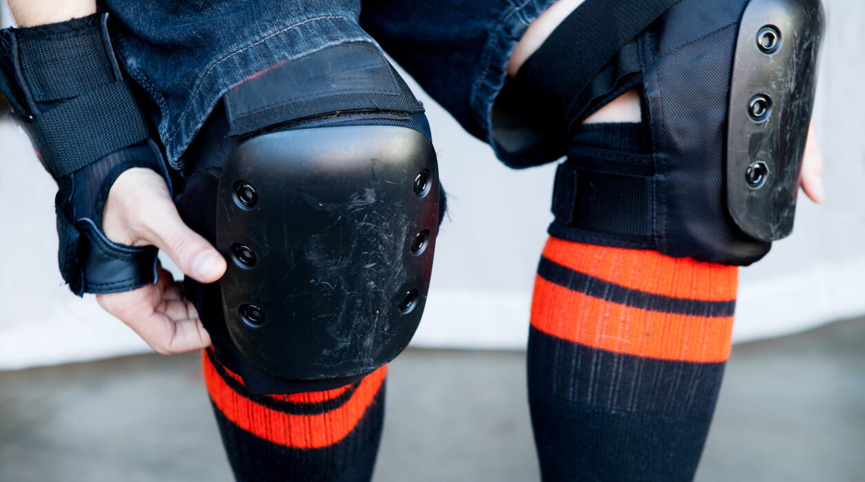 This is an image of an unidentified man wearing a pair of protective knee pads in color black. He is also wearing a black with orange detailed pair of socks.