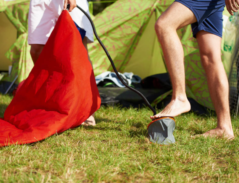 Cropped photo of two people inflating mattress with a pump in front of their tent.