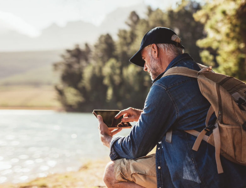 This is an image of a man, reading something in his tablet, sitting near a lake, wearing a brown backpack.