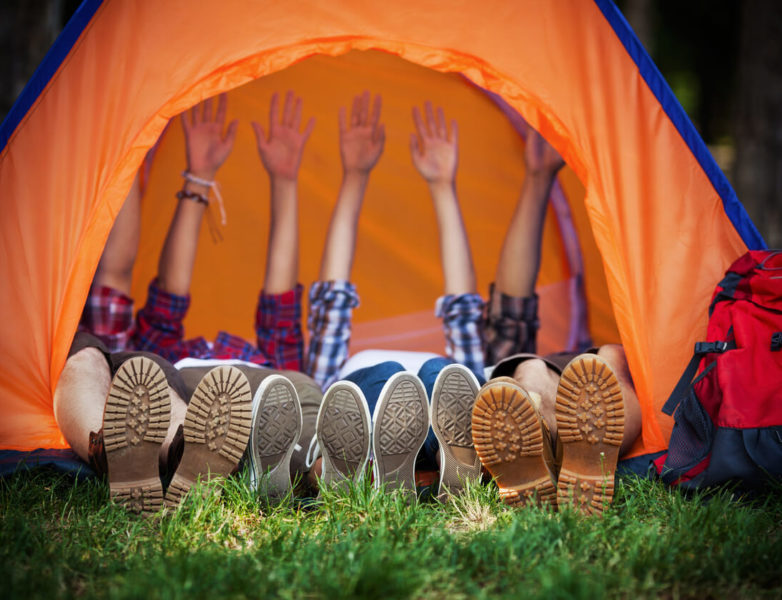 Photo of campers lying down in a tent with their hands up.