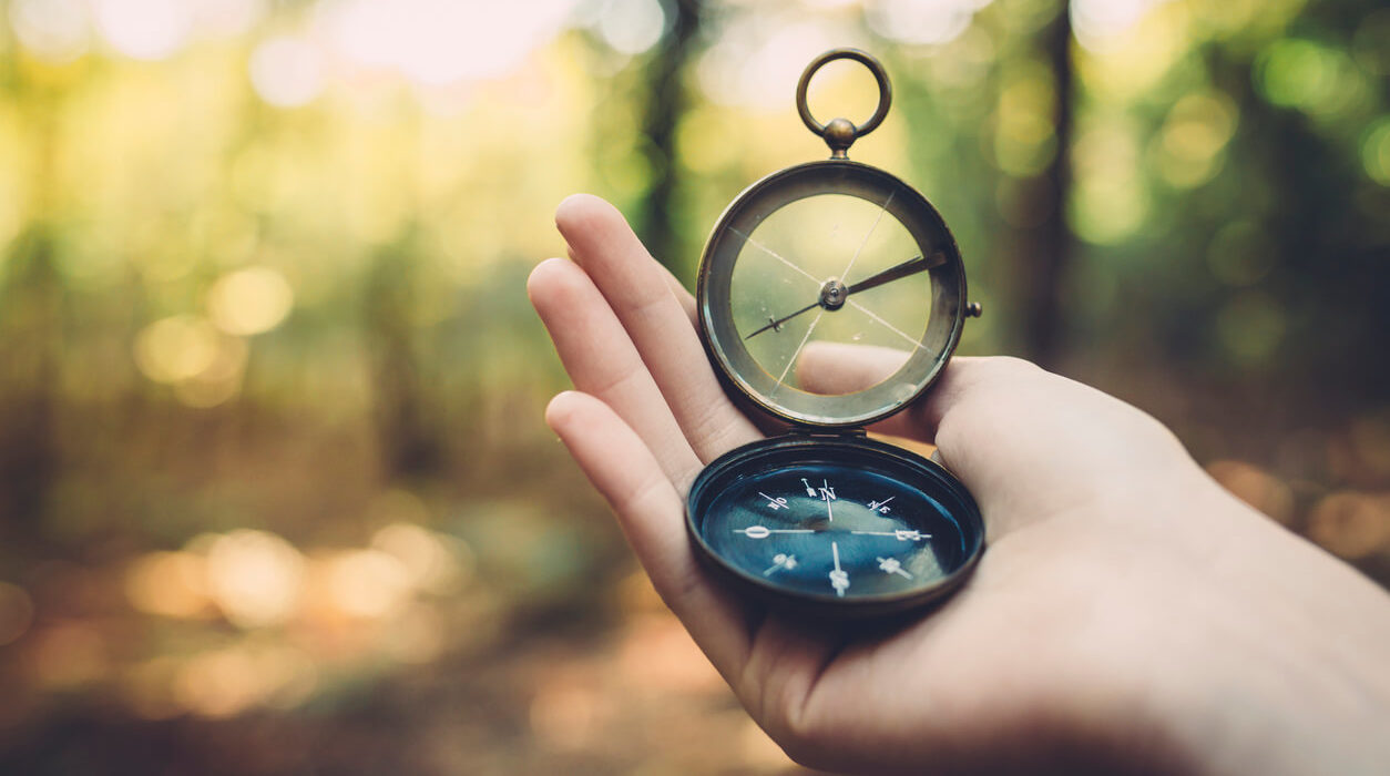 Image of a hand, a survival compass in a palm, with blurred woods background.