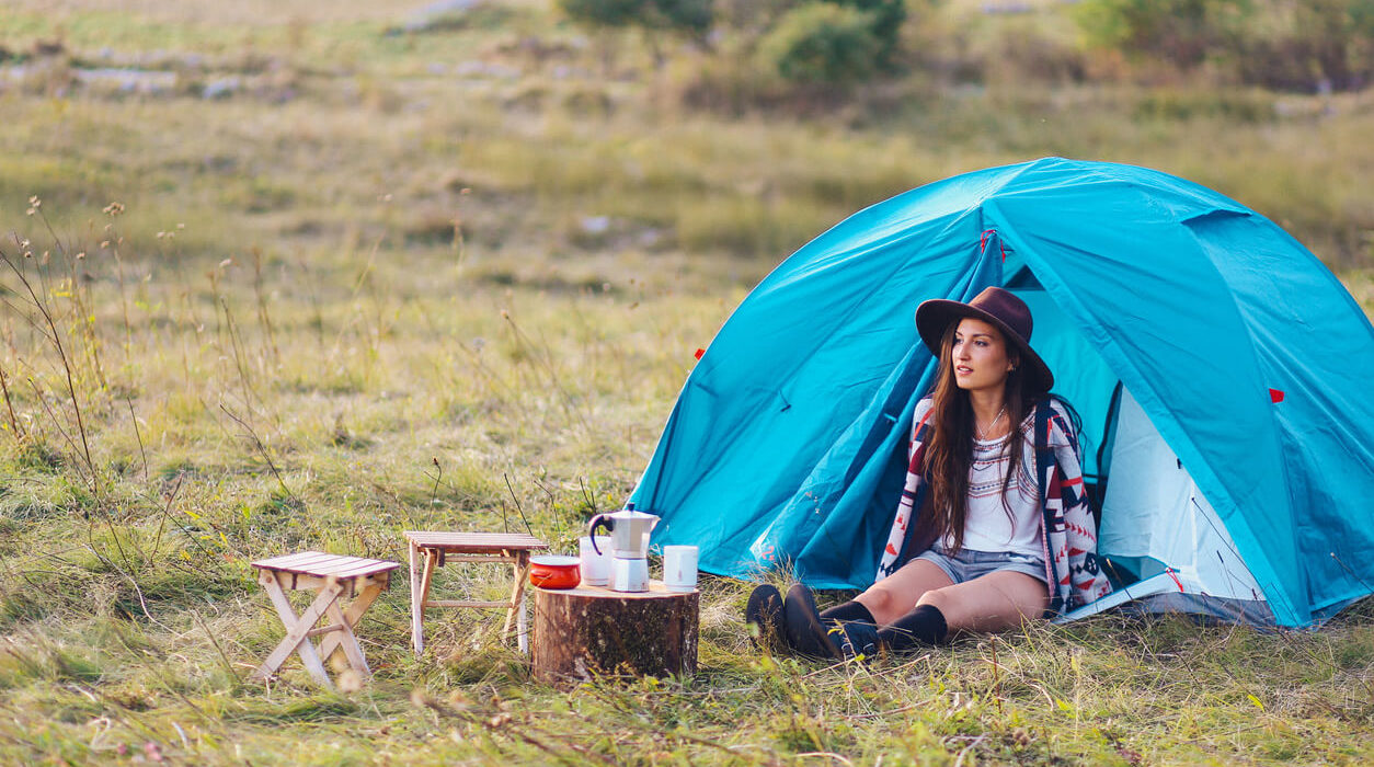 An image of a woman, camping, with a coffee maker near her, and a camp tent behind her.
