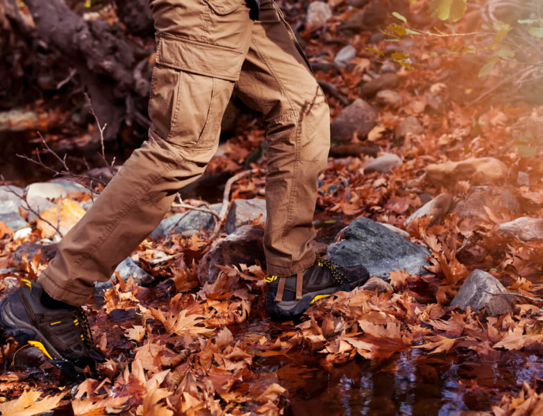 This is an image of a man running in the forest, wearing a brown tactical pants.