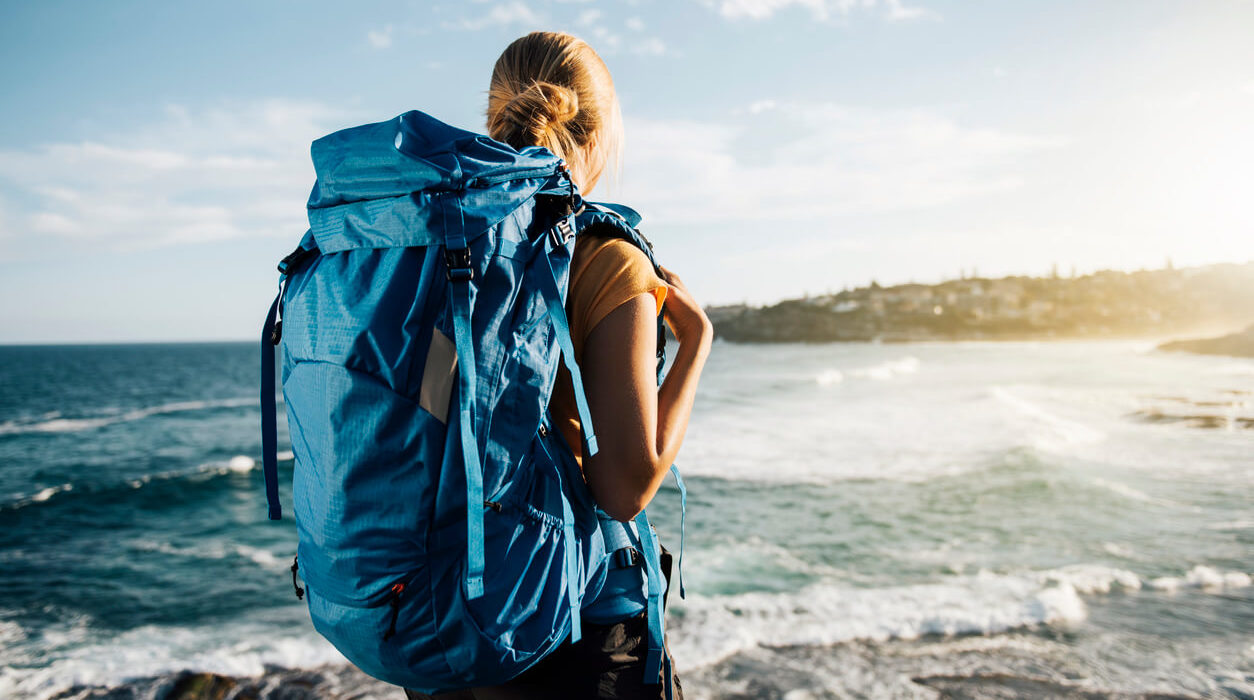 Image of a woman with a backpacking bag looking over the sunset.