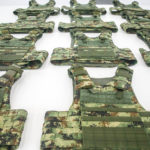 Image of lined tactical vests in green camouflage color.