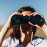 A photo contains a woman looking through a pair of black binoculars.