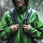 Photo of a man wearing green raincoat at a rainy street