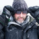 Image of a man wearing a black insulated jacket adjusting his sunglasses on an icy weather.
