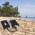 Photo of a phone and Battery solar energy lies on wooden log with a sandy beach background