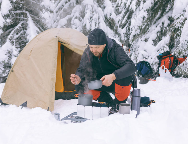 Photo of a man making food in front of his tent in a snow field.