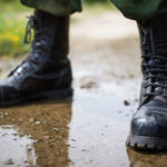 This is a close-up image of a pair of feet wearing tactical boots on a muddy ground.