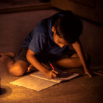 Image of a boy studying under lamp