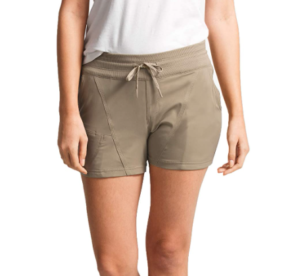 This is an image of an unidentified woman standing, wearing a hiking short, above the knee, in light brown color, belt lace tied into a ribbon.
