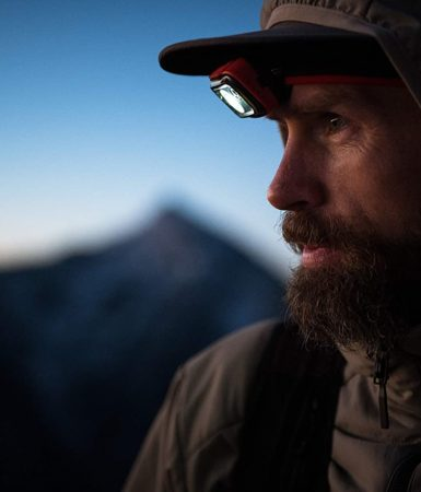 Close-up photo of a man wearing a hat and the Black Diamond Spot 325 headtorch on a dusky setting.