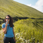 This image contains a woman at the trail drinking water from her hydration bladder that is inside her backpack.