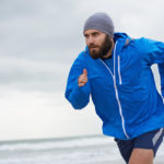 This is a photo of a man wearing a blue running jacket at the beach.